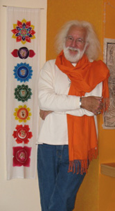 Doug von Koss, in saffron scarf, stands next to chakra banner.