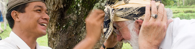 A smiling Balinese man helps Doug von Koss tie on a beautiful patterned head wrap.