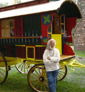 Doug von Koss leaning against a brightly painted yellow and red gypsy caravan at the 2006 Minnesota Men's Conference.